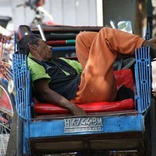 Locale bewonder ligt te slapen in zijn fietstaxi