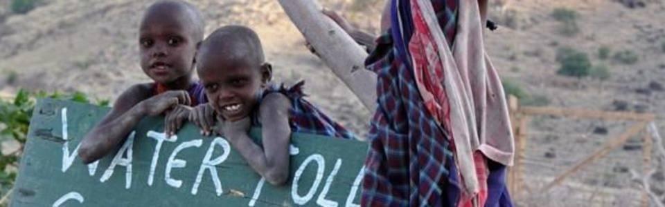 Tanzaniaanse kinderen verkopen water langs de weg