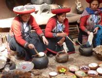 Traditioneel geklede vrouwen kleuren het geweefde wol in Maras, Peru