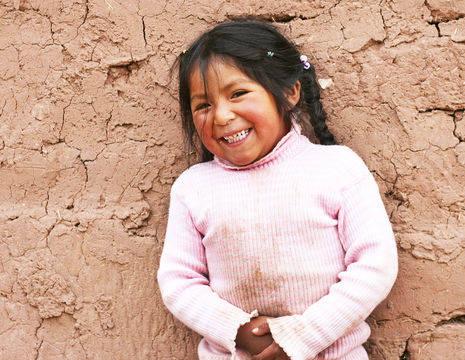 Vrolijk meisje in het authentieke dorp Guamote