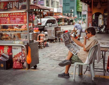 Local naast zijn kraampje in Chinatown